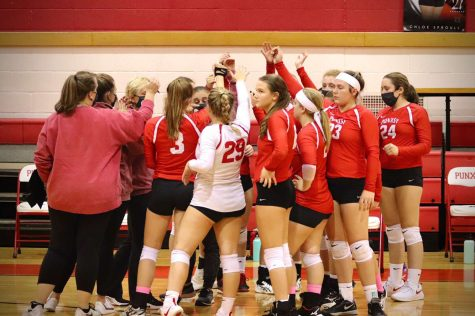 The Varsity volleyball players huddle up after winning a game during the regular season.