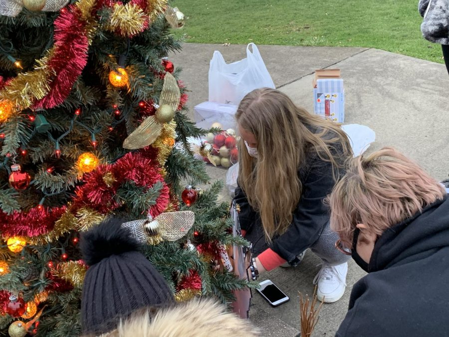 Art Club members (from left to right: Eliza Neal [Treasurer], Madilyn Fye, Michael Frantz) place brooms at the bottom of the tree.