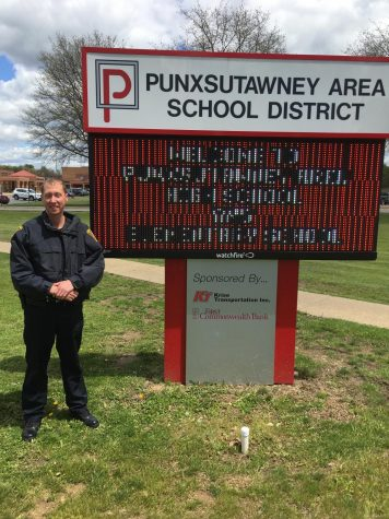 Officer Miller stands in front of the PASDs digital sign, which reads, Welcome to Punxsutawney Area High School and Elementary School.