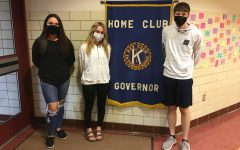 (from left) Juniors Savannah Welder, Libby Gianvito, and Preston Martz stand in front of the Key Club banner at the school entrance.